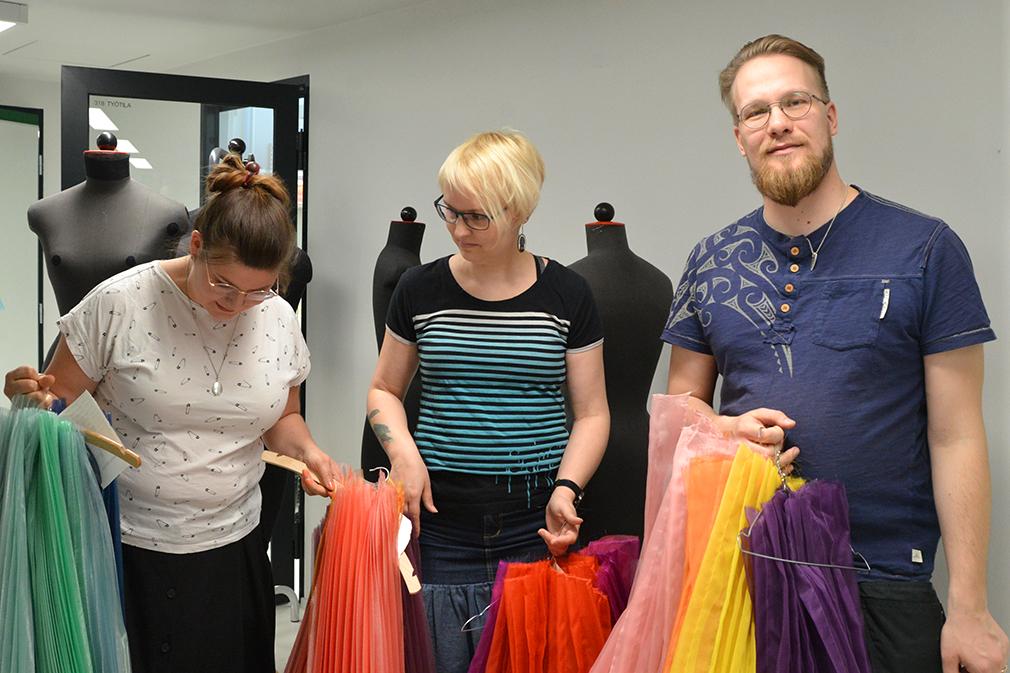 Riikka Canth, Anni Laanti ja Aati Saarva esittelevät pukuihin tulevia silkkejä. – Silkki on kevyt materiaali, vaikkakaan ei kestävin, Riikka kertoo materiaalien tuomista haasteista.