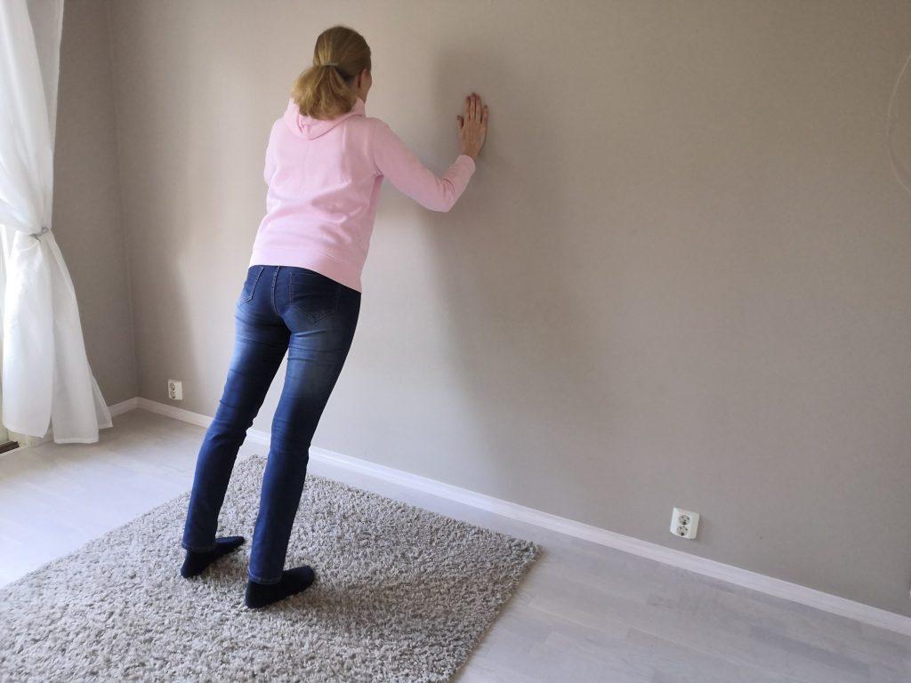 Nainen punnertaaa seinää vasten