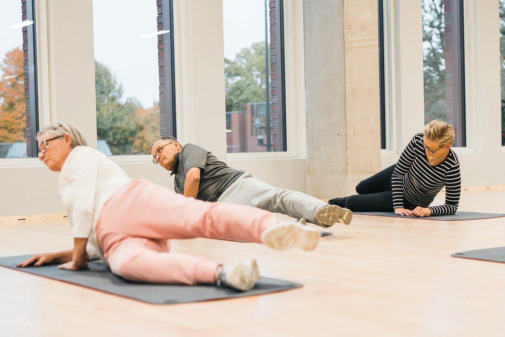 Kolme ihmistä vahvistaa pakaralihaksia lattialla