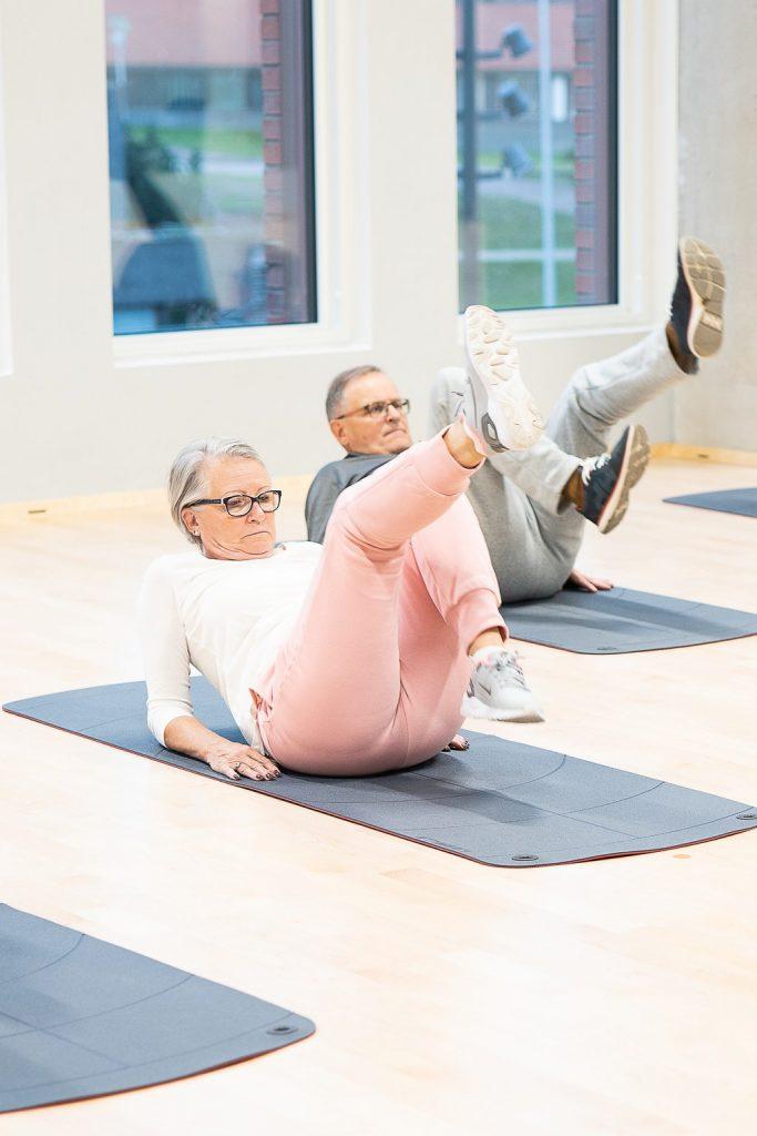 Nainen ja mies tekevät alavatsaliikettä lattialla.