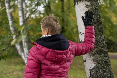 Nainen venyttelee rintalihasta puuta vasten
